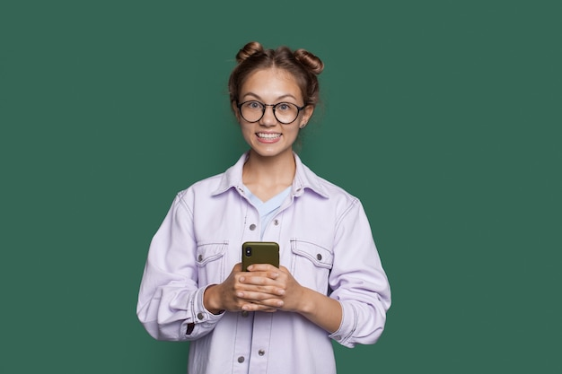Menina loira caucasiana está sorrindo com os dentes para a câmera em uma parede verde segurando um celular e usando óculos