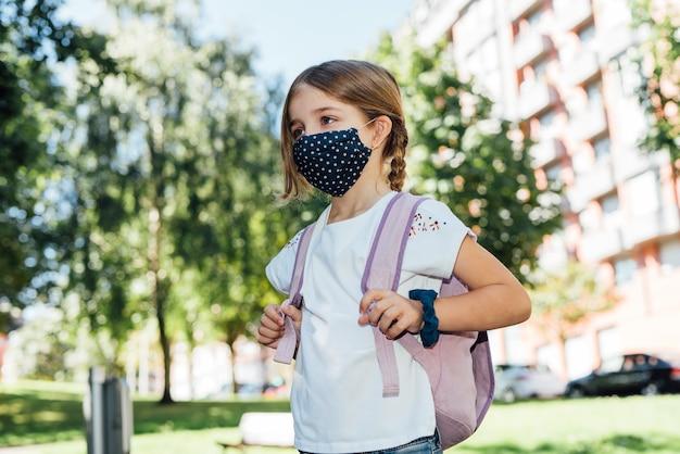 Menina loira caucasiana que vai para a escola no início do ano com uma máscara no rosto por causa da pandemia de coronavírus covid19