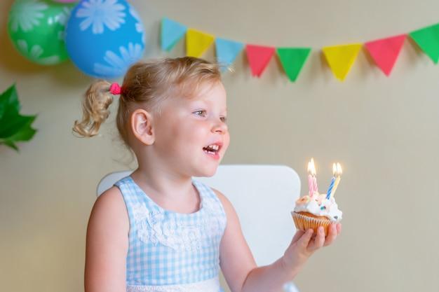 Menina loira, caucasiana, sorrindo enquanto olha para um bolo festivo com velas.