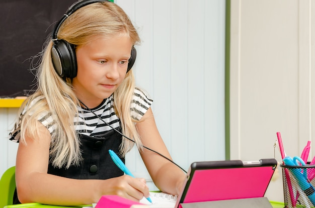 Menina loira caucasiana, tendo aulas online. conceito de educação em casa