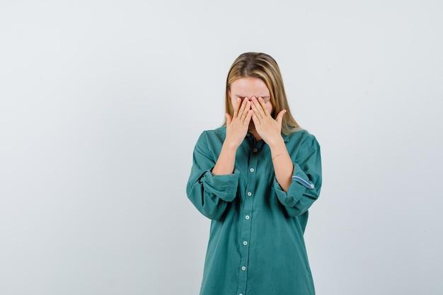 Menina loira cobrindo o rosto com as mãos na blusa verde e parecendo cansada.