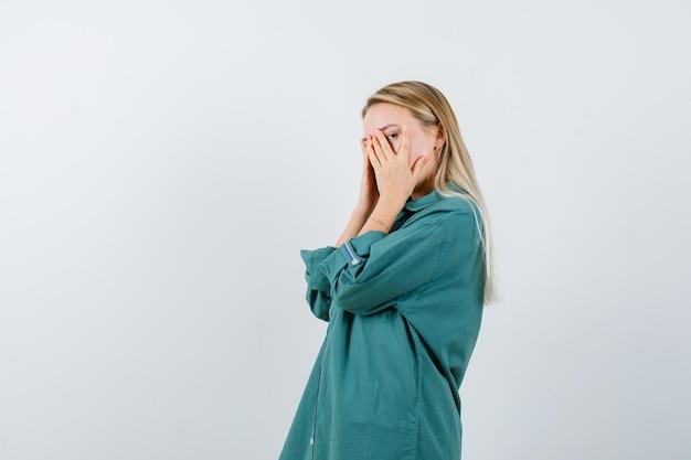 Menina loira cobrindo o rosto com as mãos, olhando por entre os dedos na blusa verde e olhando sério.