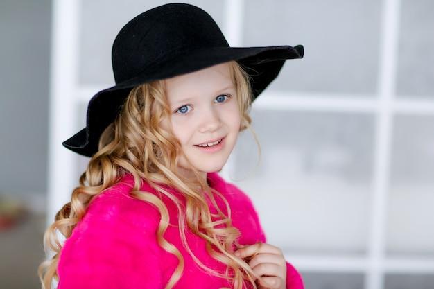 Menina loira colegial com cabelos cacheados com um chapéu preto na cabeça