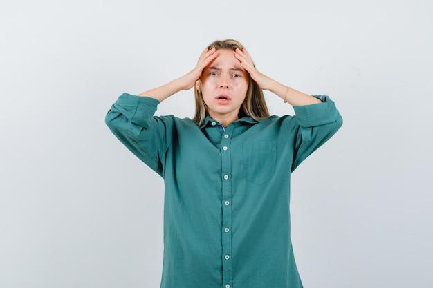 Menina loira colocando as mãos na cabeça na blusa verde e parecendo chocada.