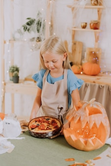 Menina loira com avental na cozinha decorada com abóboras para o halloween preparando uma torta de focaccia