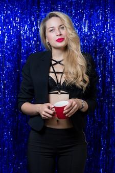 Menina loira com batom vermelho nos lábios e um copo vermelho nas mãos dela está de pé com uma roupa preta contra os brilhos azuis