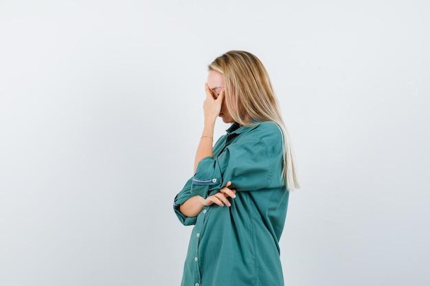 Menina loira com blusa verde cobrindo o rosto com a mão e parecendo cansada