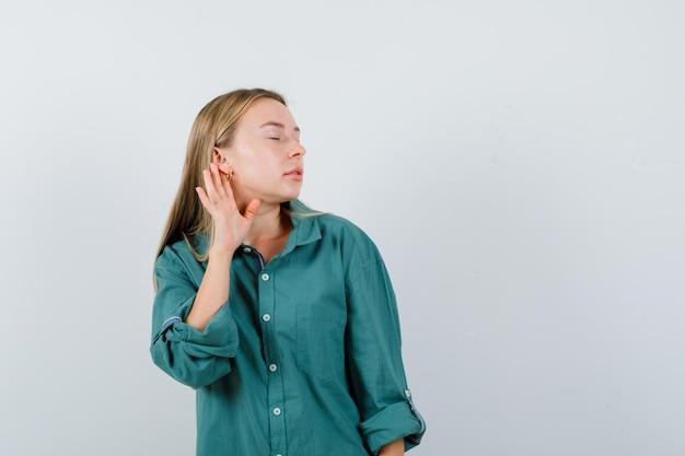 Menina loira com blusa verde segurando a mão perto da orelha para ouvir algo e parecendo focada
