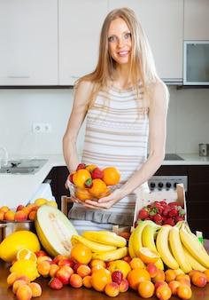 Menina loira com cabelos longos com montes de várias frutas
