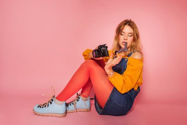 Menina loira com câmera de filme estilo retro em fundo rosa
