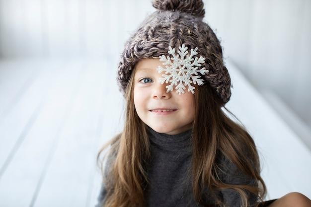 Menina loira com chapéu de inverno e um floco de neve
