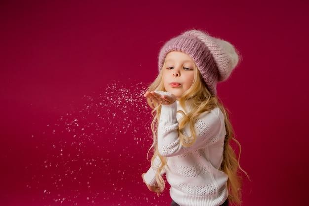 Menina loira com chapéu de malha e blusa brinca com a neve