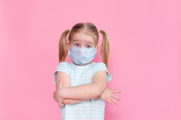 Menina loira com dois ponytales em um rosto de máscara médica em um espaço rosa, abraçando-se com as mãos