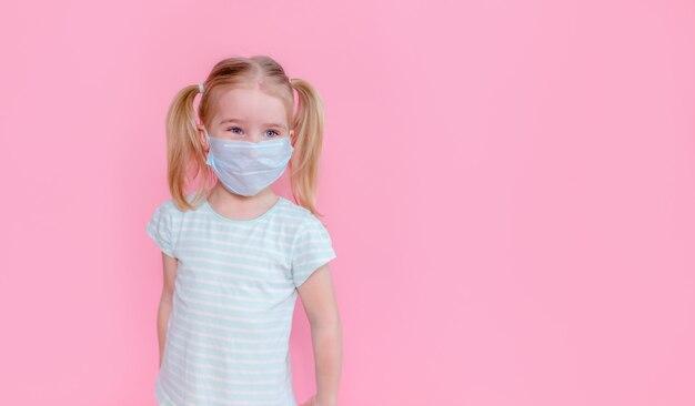 Menina loira com dois ponytales em um rosto de máscara médica em um espaço rosa. copyspace