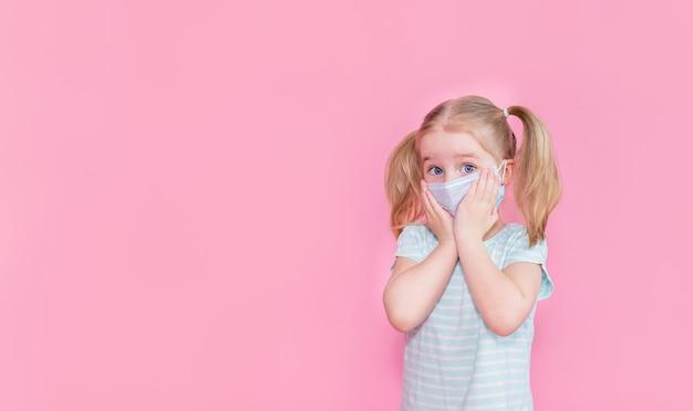 Menina loira com dois ponytales em um rosto de máscara médica em um espaço rosa, segurando as bochechas com as mãos. copyspace. amd
