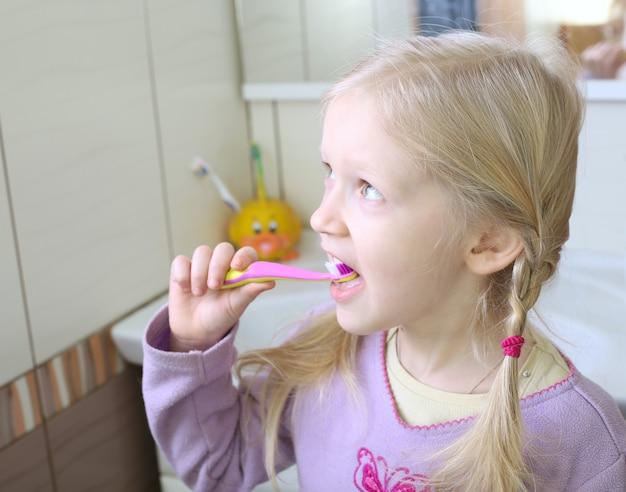 Menina loira com escova de dentes