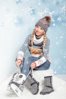 Menina loira com longas tranças vestindo patins, apertando os cadarços. patinação no gelo no inverno