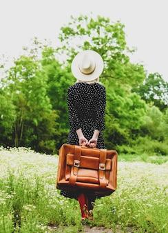 Menina loira com mala e chapéu em campo de flores de camomila no verão