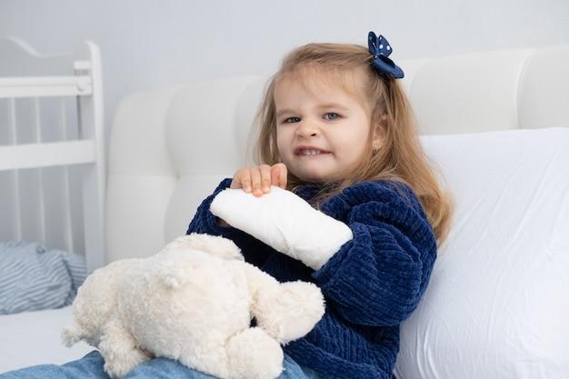 Menina loira com mão engessada, sentada na cama.
