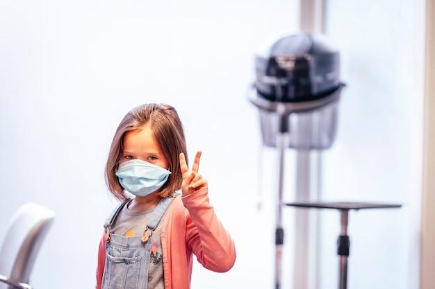Menina loira com máscara muito feliz após o corte de cabelo no cabeleireiro. reabertura com medidas de segurança para cabeleireiros na pandemia de covid-19