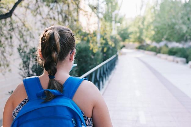 Menina loira com mochila azul e máscara facial a caminho da escola