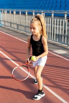 Menina loira com raquete de tênis e bola
