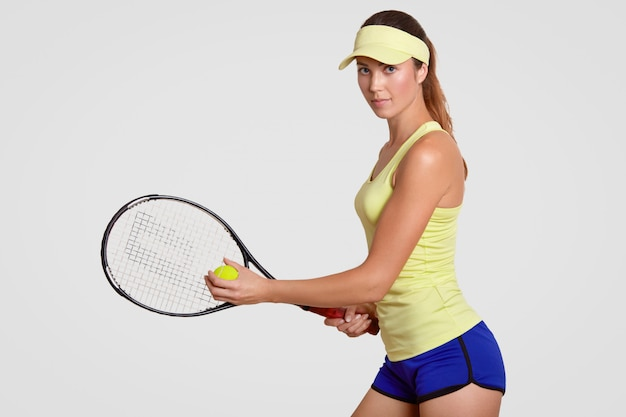 Menina loira com raquete e bola de tênis