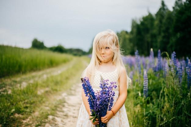 Menina loira com rosto expressivo, posando com buquê de flores do campo na natureza de verão
