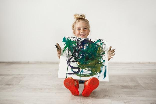 Menina loira com rosto sardento e cabelo bun mostrando imagens para seus pais.