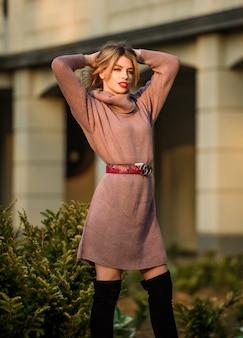 Menina loira com roupa de outono. enfatize a cintura com o cinto de alça. conceito de malhas. modelo da vogue. suéter de lã de cashmere. suéteres superdimensionados quentes. mulher usar camisola. túnica ou vestido de moletom alongado.