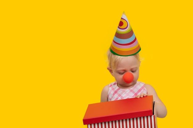 Menina loira com um chapéu festivo e nariz de palhaço segurando uma caixa de presente