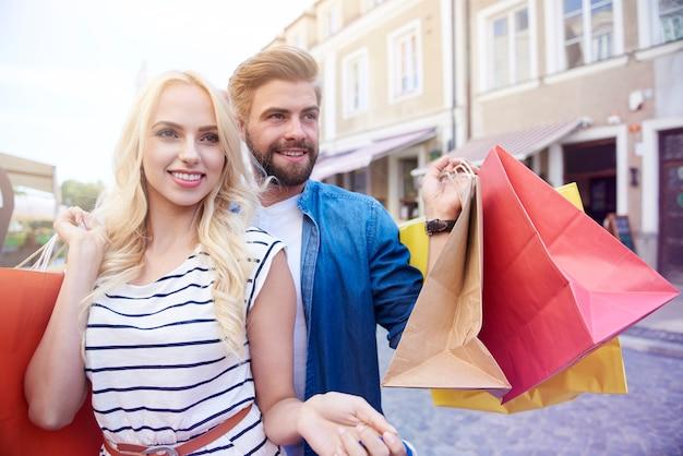 Menina loira com um homem segurando sacolas de compras
