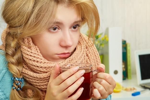 Menina loira com um resfriado em um suéter, bebendo chá quente, no fundo de uma mesa, cebola, limões, livros e um laptop
