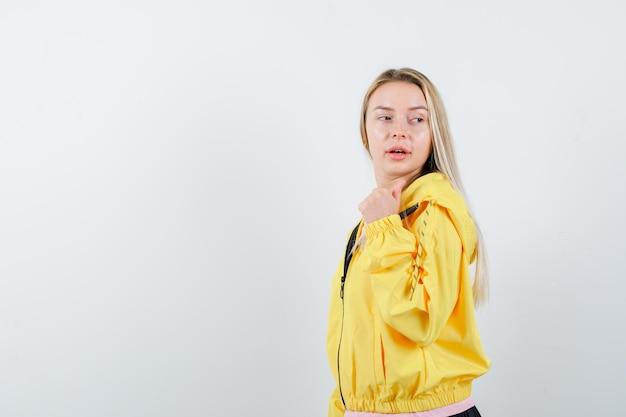 Menina loira com uma jaqueta amarela apontando para trás com o polegar, olhando por cima do ombro e parecendo atraente.