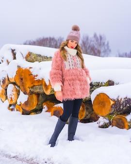Menina loira com uma jaqueta de pele rosa e um chapéu roxo na neve. ao lado de algumas árvores cortadas com gelo, estilo de vida de inverno
