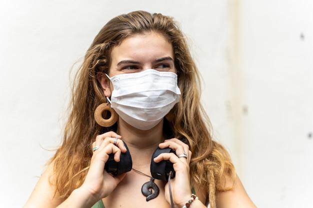 Menina loira com uma máscara no rosto para protegê-la de vírus