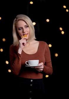 Menina loira com uma xícara de café e biscoito de gengibre na parede com luzes de fada