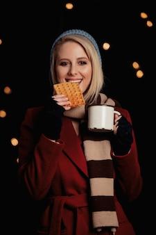Menina loira com uma xícara de café e waffle