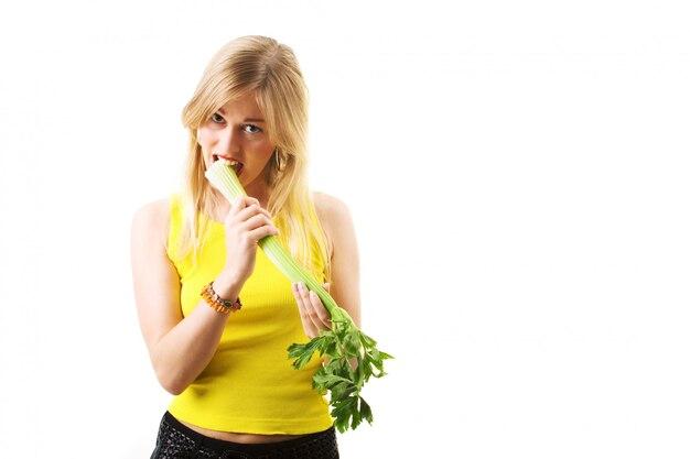 Menina loira comendo aipo