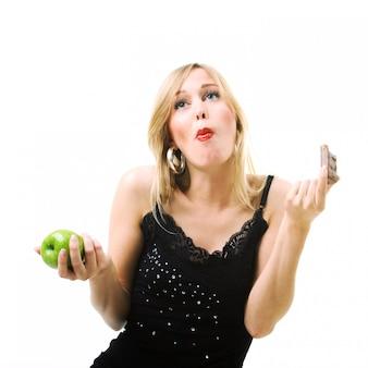 Menina loira comendo chocolate em vez de maçã