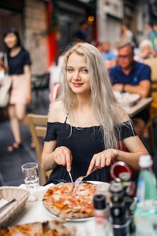 Menina loira comendo uma pizza