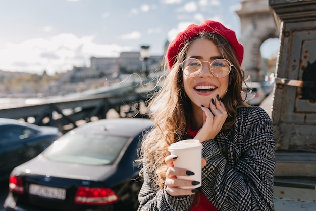 Menina loira curiosa com uma boina vermelha elegante posando com um sorriso no fundo desfocado na manhã de vento