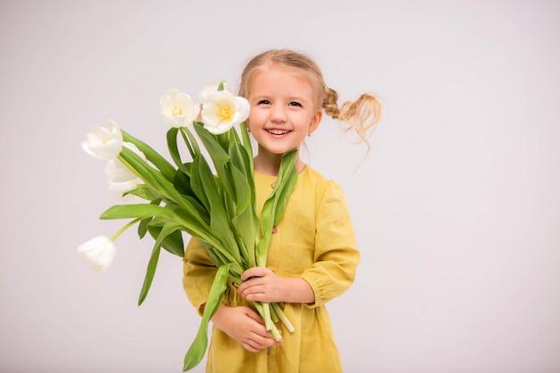 Menina loira da criança no vestido verde com tulipas no fundo branco