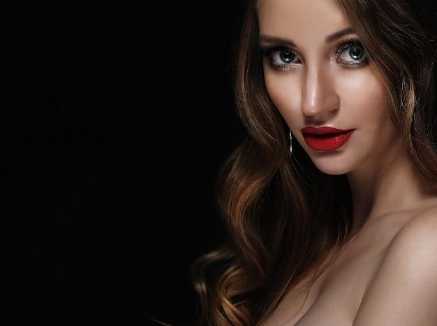 Menina loira da moda com cabelo encaracolado comprido e brilhante. lábios vermelhos e maquiagem brilhante. sobre fundo preto.