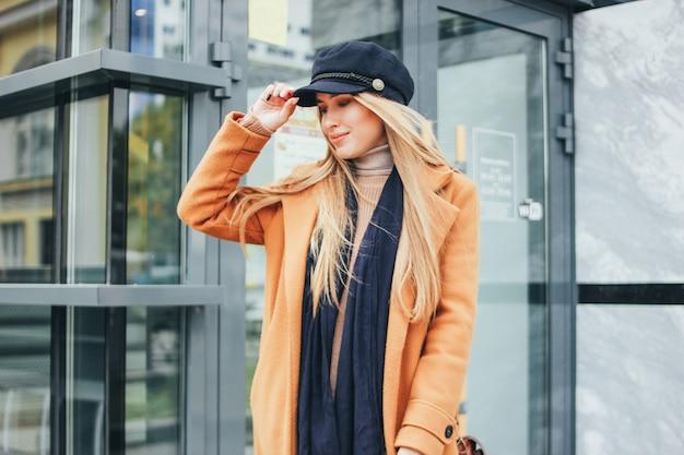 Menina loira de cabelo comprido bonito na moda em casaco marrom e boné azul na cidade, estilo de rua