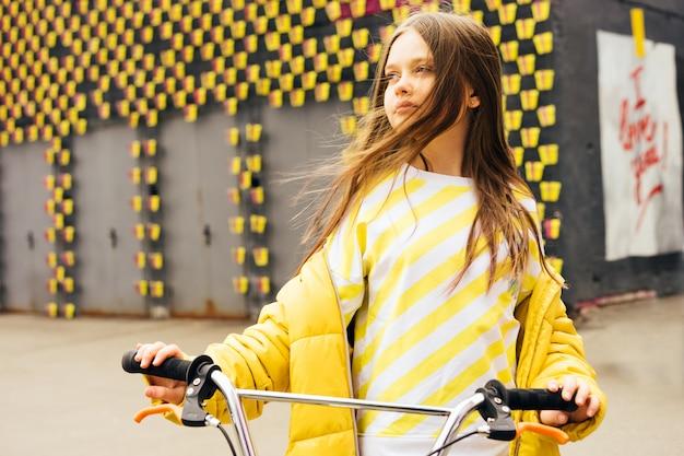 Menina loira de cabelo comprido em uma camisola amarela e jaqueta amarela