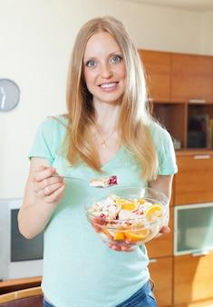 Menina loira de cabelos compridos comendo salada de frutas