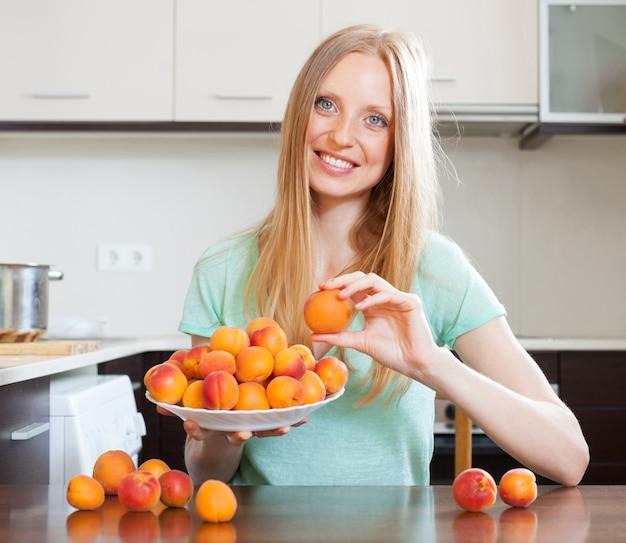 Menina loira de cabelos compridos segurando damascos na cozinha doméstica