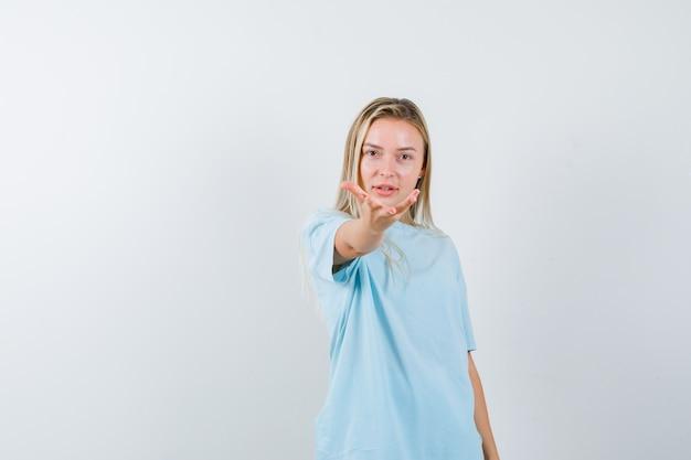 Menina loira de camiseta azul, esticando a mão em direção à câmera, segurando algo e olhando sério, vista frontal.