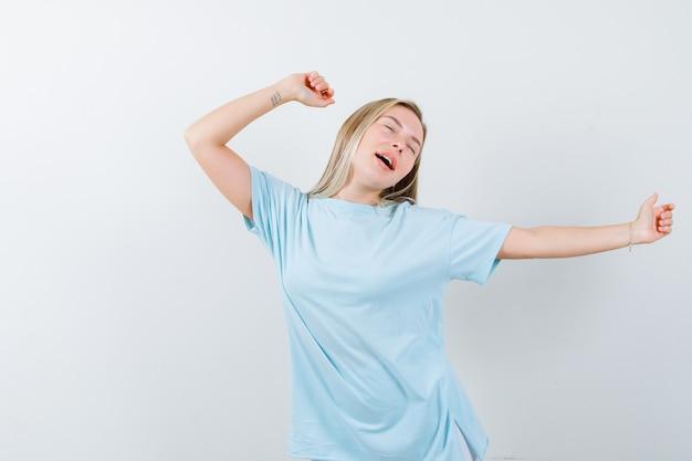 Menina loira de camiseta azul, se esticando e bocejando, mantendo os olhos fechados e parecendo com sono, vista frontal.